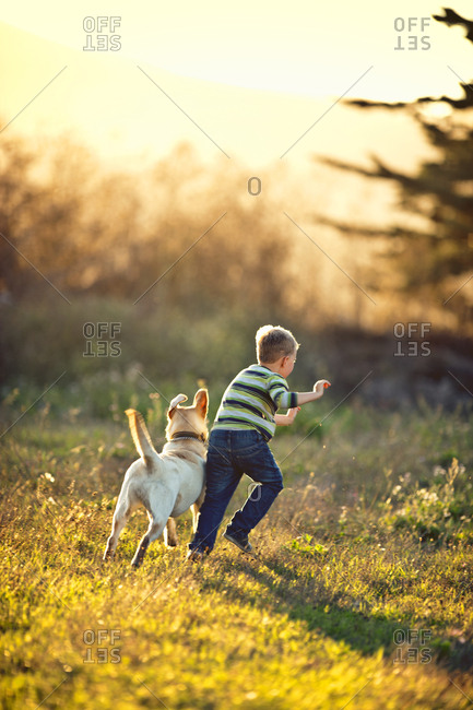 Little boy running on the field with his dog.