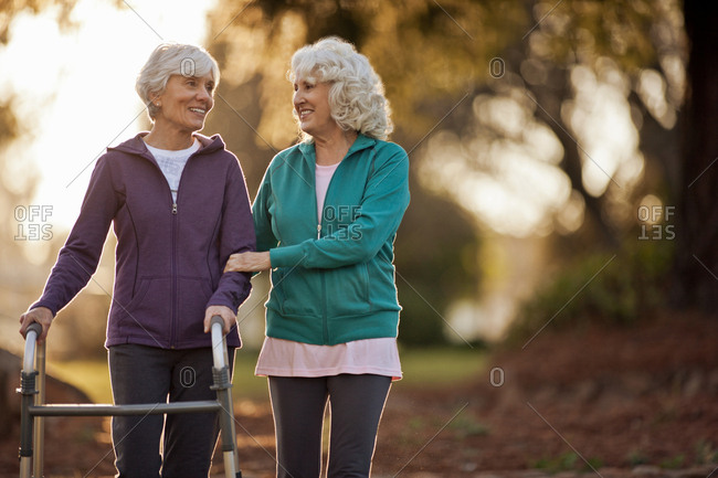 Smiling senior woman helping her friend to walk with a walking aid through a park.