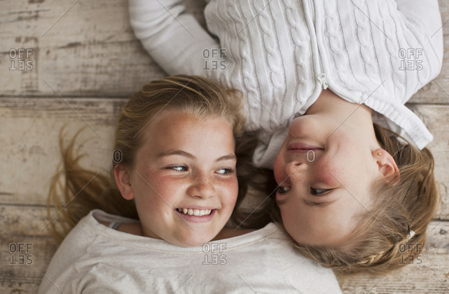 Two sisters smiling at each other while lying side by side on a hardwood floor.