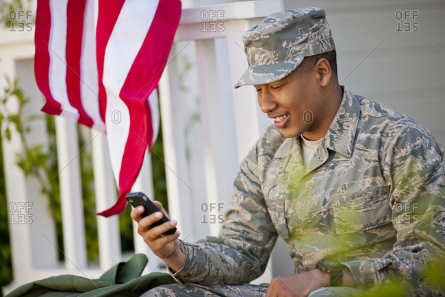 Smiling young army soldier sending a text message outside his home.