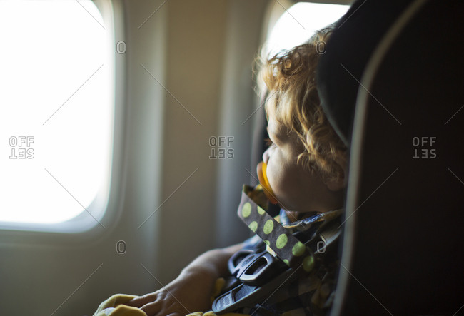 Young boy sitting in a car seat in an airplane cabin.