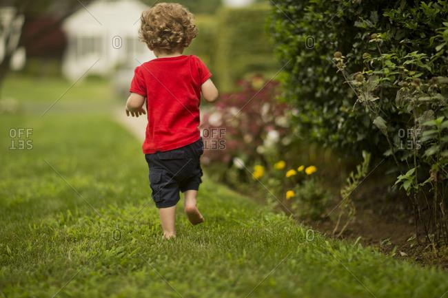 Young boy walking in a back yard.