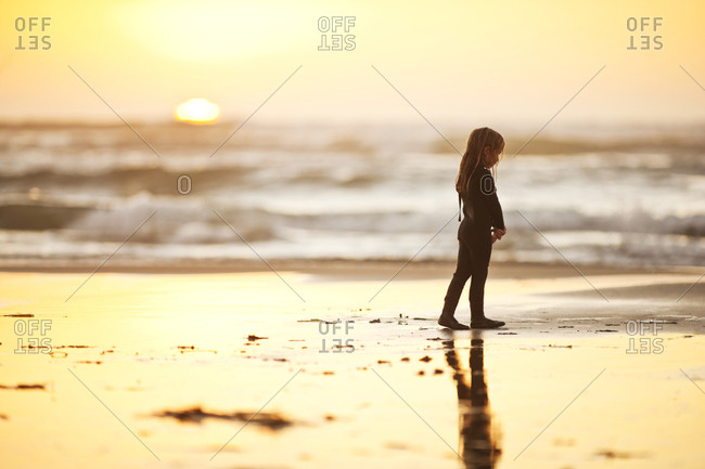 Young girl standing on a beach wearing a wetsuit.