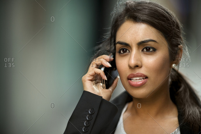 A Mid adult businesswoman talking on a cell phone while looking worried.