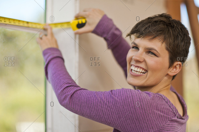 Mid adult woman smiling while using a tape measure.