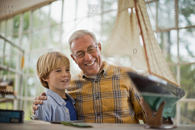 Satisfied senior man and his grandson looking at the toy boat they built together.