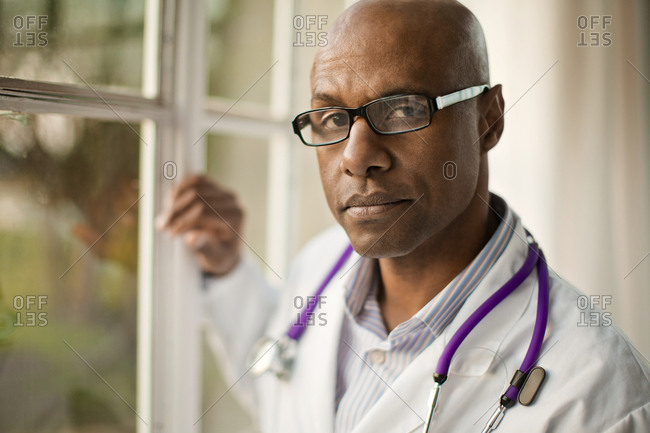 Portrait of a serious male doctor leaning against a window frame.
