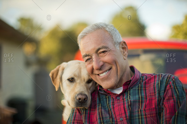 Portrait of a smiling senior man with his dog.