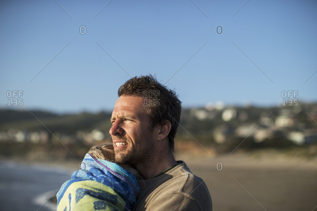 Concerned mid adult man holding his daughter on a beach.