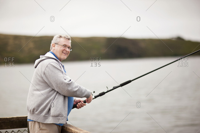 Smiling mature man fishing off a pier.