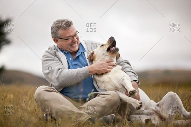 Smiling mature man playfully petting his dog.