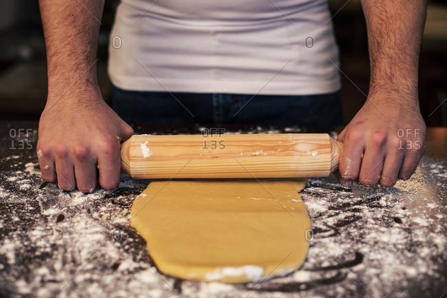 Mid section of the hands of an unrecognizable man kneading dough with a rolling pin on a brown table at home