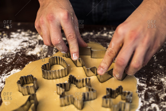 Mid section of the hands of an unrecognizable man making gingerbread cookies on a brown table at home
