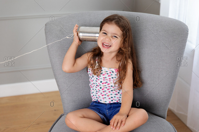 Laughing girl sitting on chair listening to toy telephone made with tin can and string