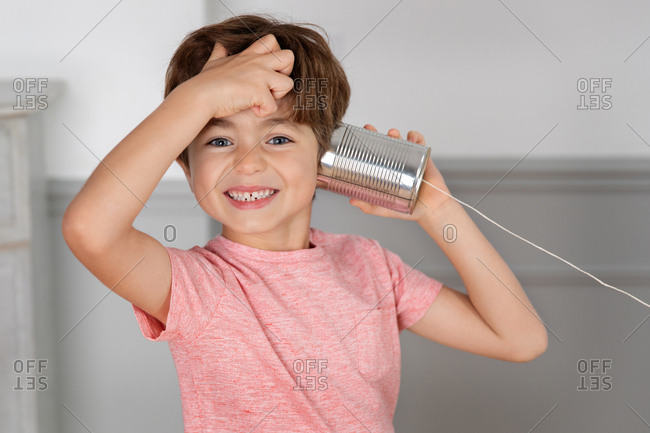 Smiling boy listening to toy telephone made with tin can and string