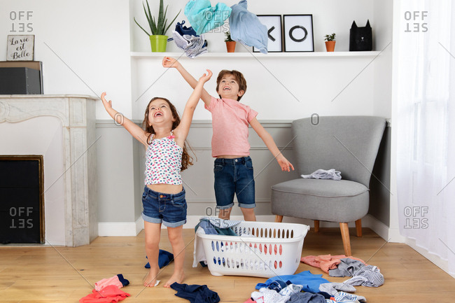 Laughing children throwing clothes in the air from laundry basket