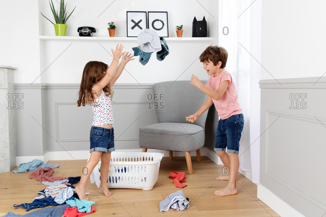 Children throwing clothes out of laundry basket