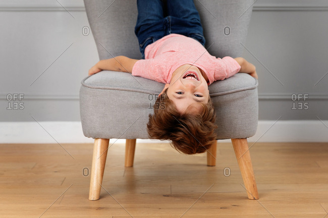 Portrait of laughing boy lying upside down on chair