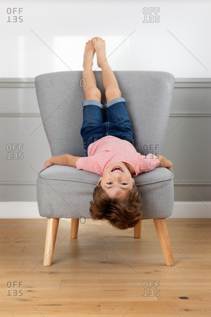 Laughing boy lying upside down on chair