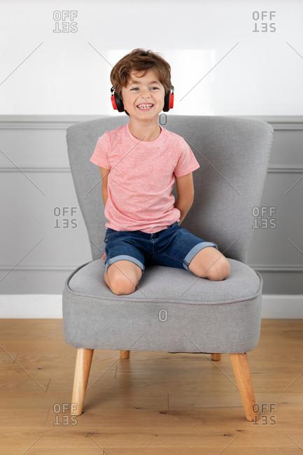 Smiling boy wearing headphones sitting on chair