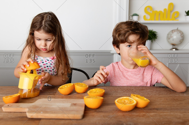 Girl juicing oranges while her brother drinks freshly squeezed orange juice