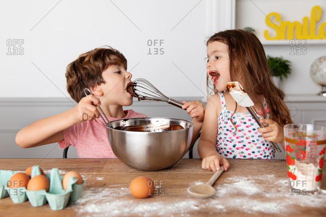 Children making brownies together in kitchen