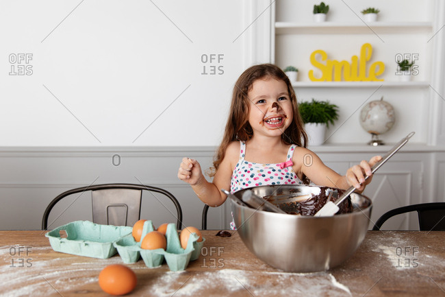 Laughing girl with messy face baking in the kitchen