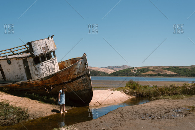 Girl exploring around beached boat
