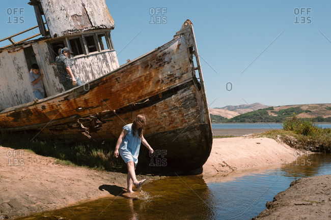 Family exploring around beached boat