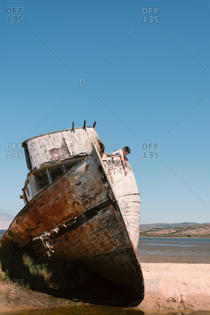 Boy exploring beached boat