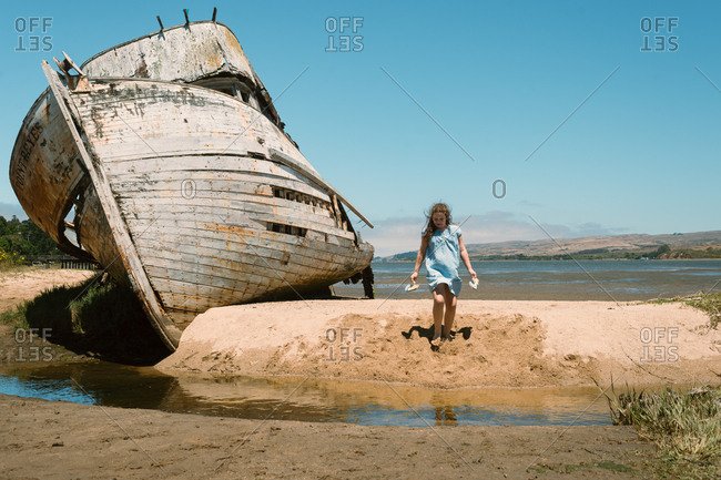 Girl exploring around abandoned boat