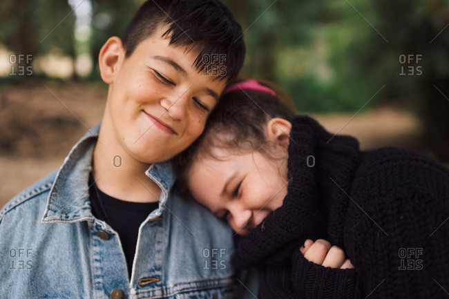 Close up of girl leaning on her brothers shoulder while walking in woods