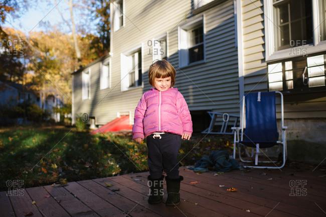 Little girl standing on backyard deck
