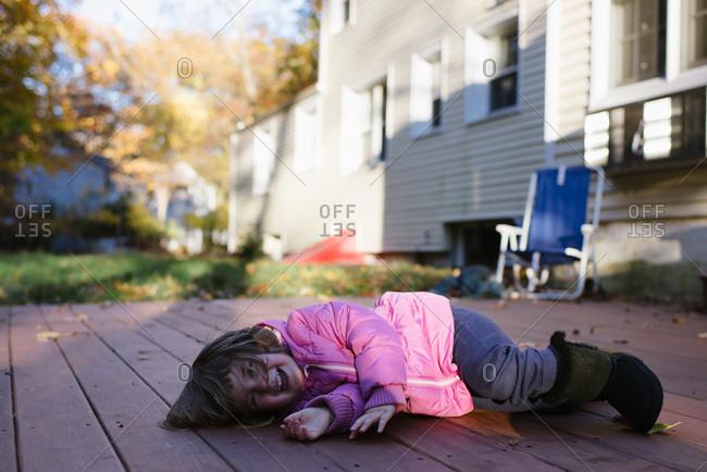 Little girl playing on backyard deck