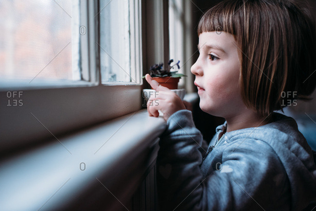 Little girl looking out a window and pointing