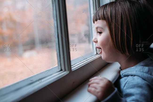 Little girl looking out a window