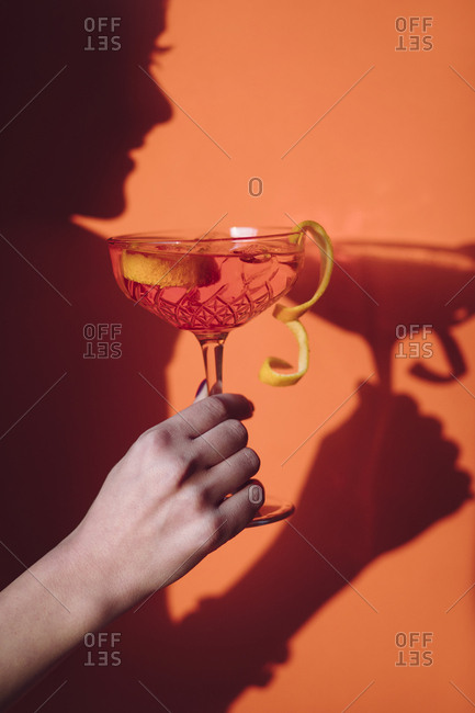 Shadow of woman holding cocktail