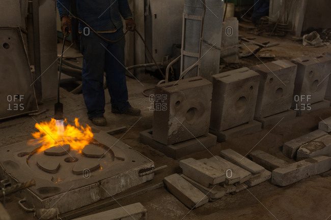 Low section of worker heating metal casting with flaming torch