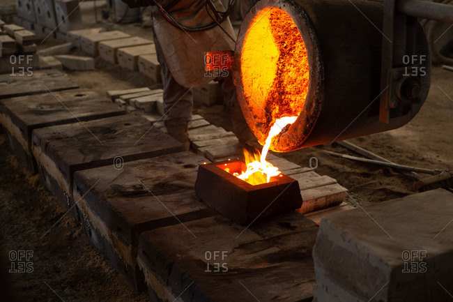 Worker pouring molten metal from flasks into molds in foundry