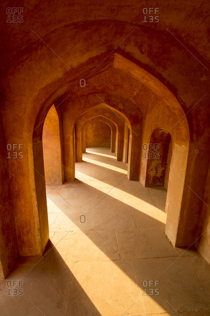 Interior arched hallway with dramatic shadows