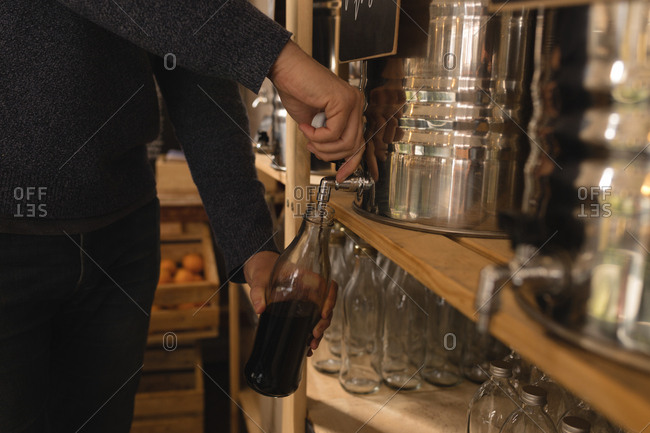 Close-up of man filling vinegar in bottle at supermarket
