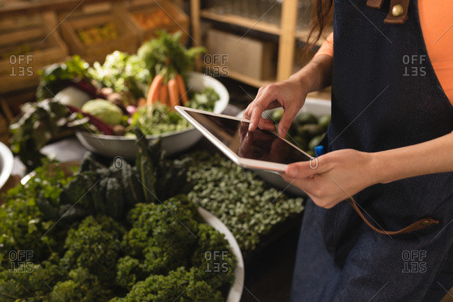 Mid section of female staff using digital tablet in supermarket