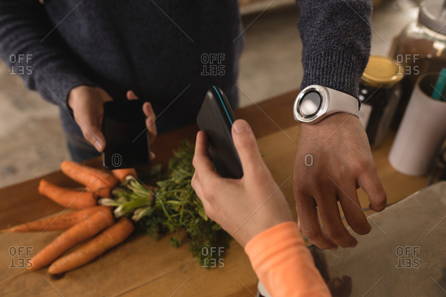 Customer making payment through smartwatch at counter in supermarket