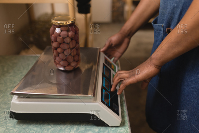 Mid section of male staff weighing jar of nuts on weighing machine