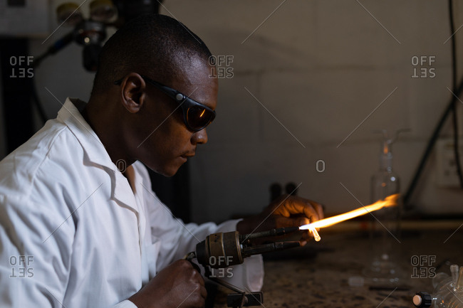 Side view of worker using welding torch in glass factory