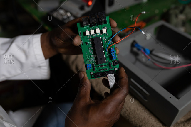 Close-up of worker examining printed circuit board in glass factory