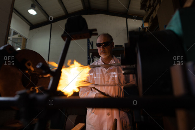 Male worker using welding torch in glass factory