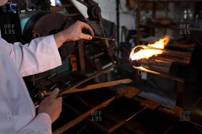 Mid section of male worker using welding torch in glass factory