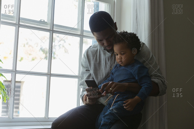 Father showing son a mobile phone in a living room at home