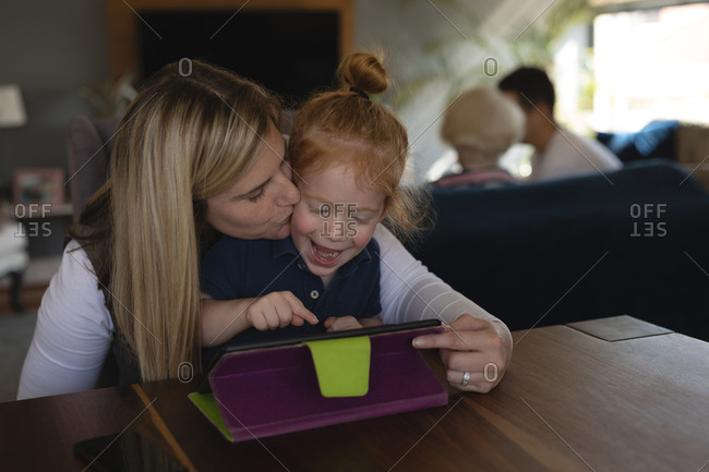 Mother kissing her daughter while using digital tablet in living room at home
